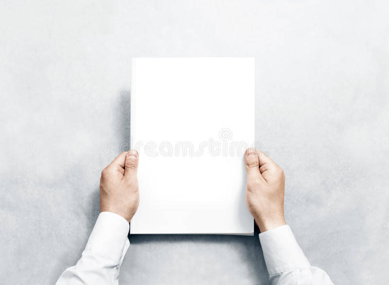 Hand holding white journal with blank cover mockup. stock images