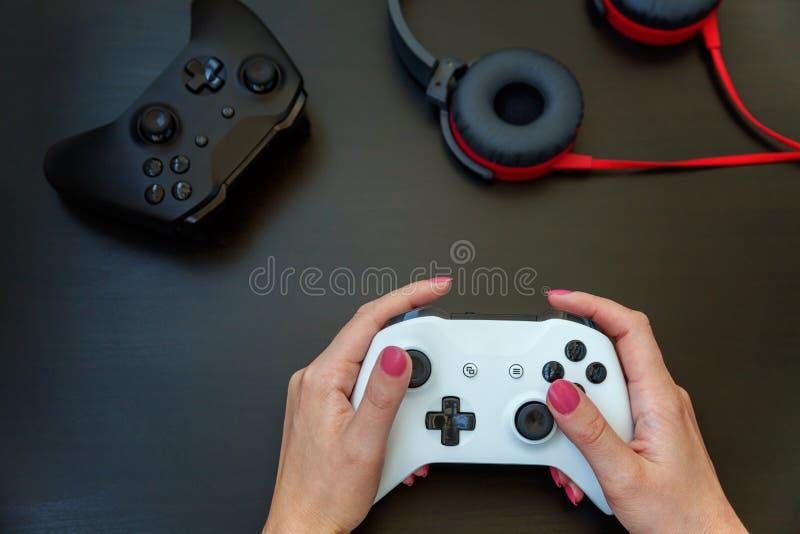 Hand holding white joystick gamepad on black background stock photography