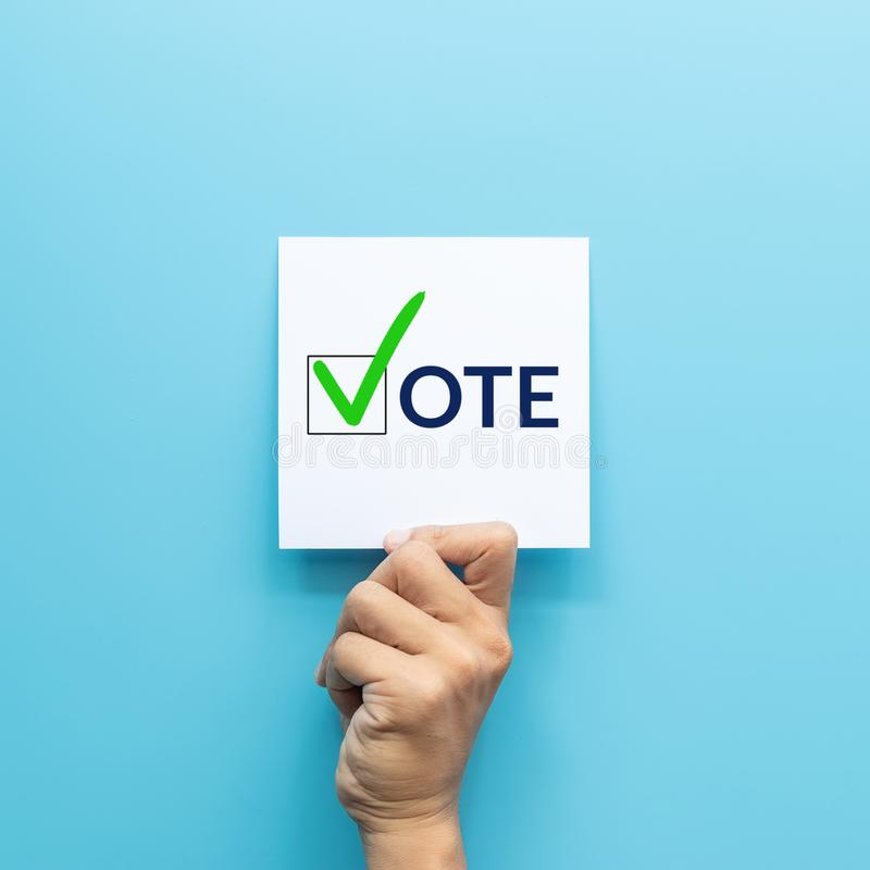Hand holding white paper with the `vote` and green check mark voting symbols in checkbox of the inscription isolated on blue royalty free stock photos