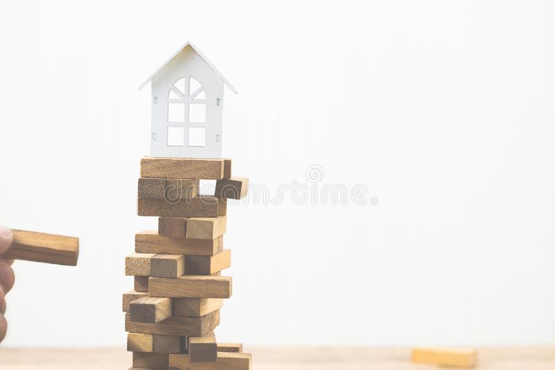 Hand holding wood block with model white house on wood block game. Investment risk and uncertainty in the real estate housing. Market. Property investment and stock photography