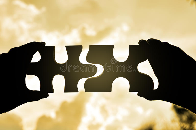 hand holding wood jigsaw piece texture pattern on nature background stock photo