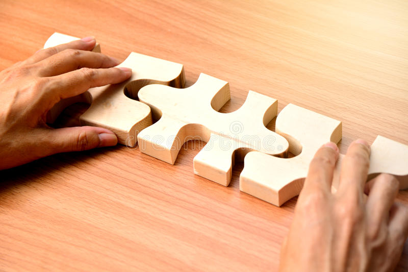 hand holding wood jigsaw piece texture pattern on wood table background stock images
