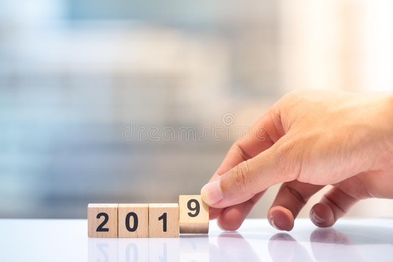 Hand holding wooden block number 9 to complete year 2019 royalty free stock photo