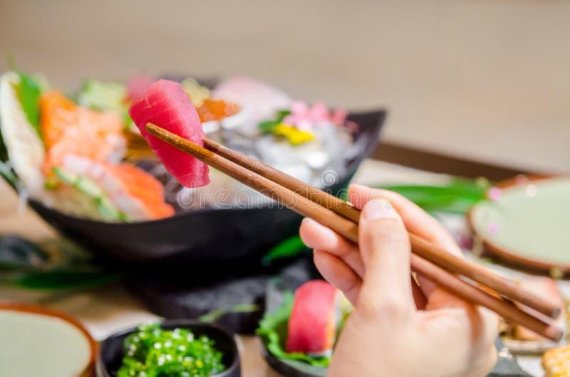 Tuna sashimi at Japanese food restaurant. Hand holding wooden chopsticks tongs Tuna sashimi at Japanese food restaurant stock photos