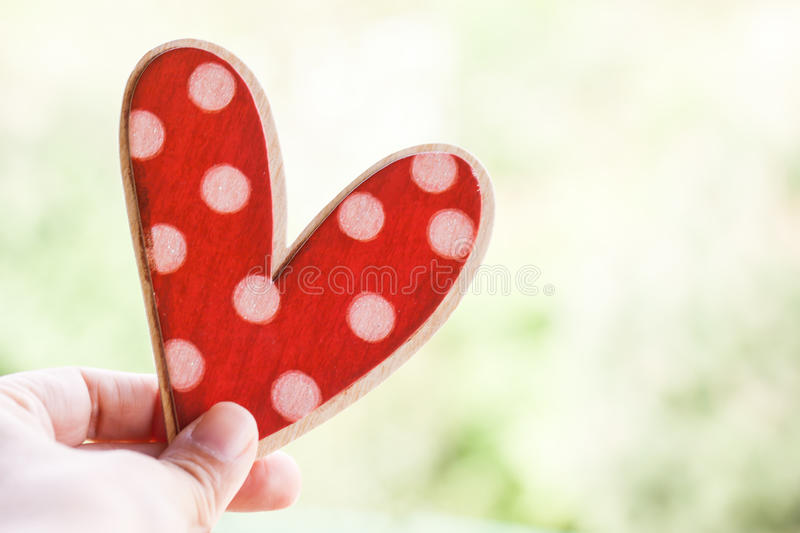 Hand holding wooden heart stock image