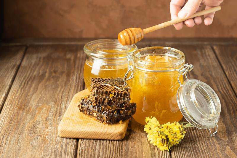 A hand is holding awooden spoon which honey flows. Banks of fresh golden flower honey on a wooden background the table. royalty free stock photo