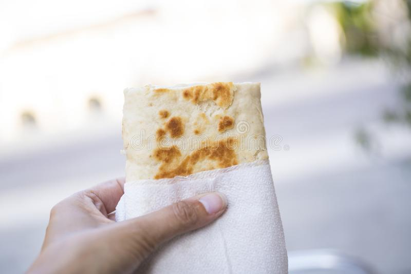 Hand holding a wrap, bread, piadina, against white blur background royalty free stock photo