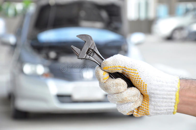 Hand holding wrench - car checking & repairing concept royalty free stock image
