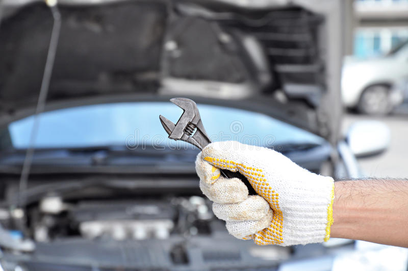 Hand holding wrench - car checking & repairing concept royalty free stock photography