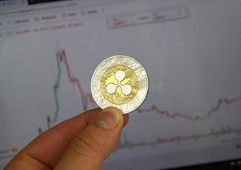 A hand holding XRP Ripple crypto currency coin. MONTREAL, CANADA - SEPTEMBER 8, 2018: A hand holding XRP Ripple crypto currency coin in a hand over a bitcoin royalty free stock photo