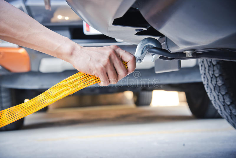 Hand holding yellow car towing strap with car. Car towing stock photo