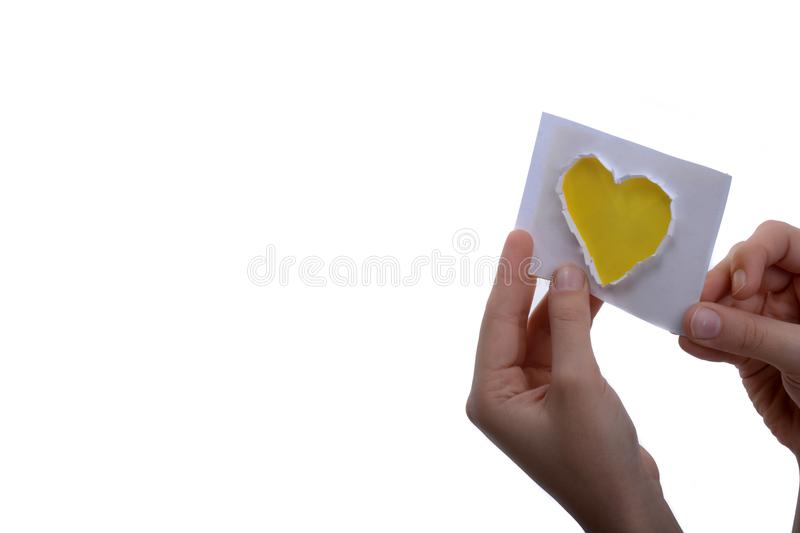 Yellow heart shape paper in hand royalty free stock photography