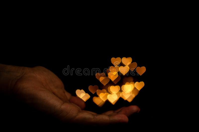 The hand holding yellow love shape bokeh light for Valentine`s day royalty free stock images