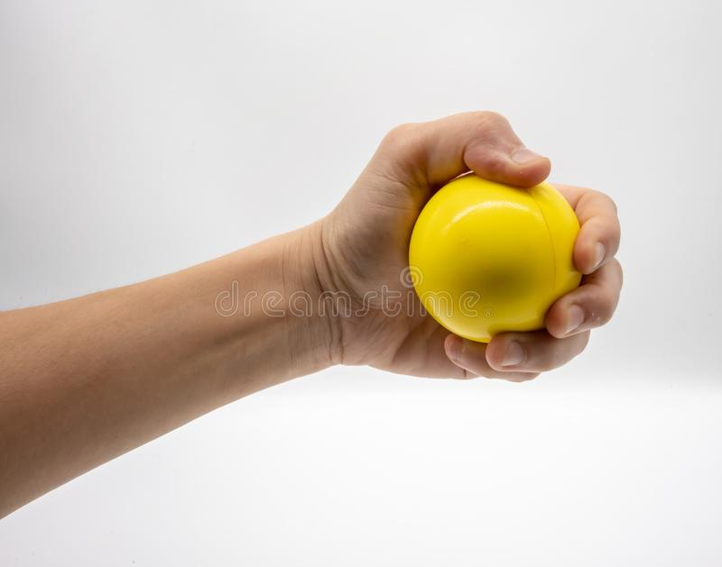 Hand holding yellow stress ball isolated on white stock photo