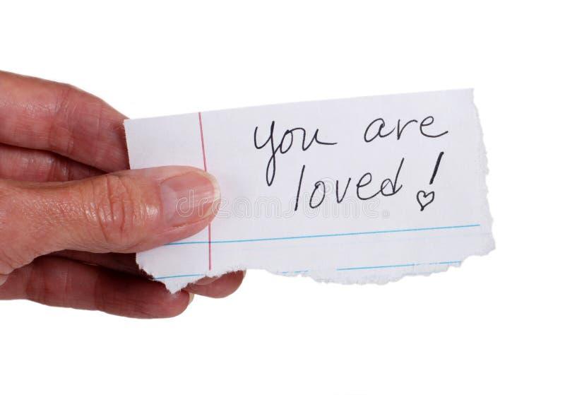 """Hand holdinganmärkningen som läser """"dig älskas"""", royaltyfria foton"""