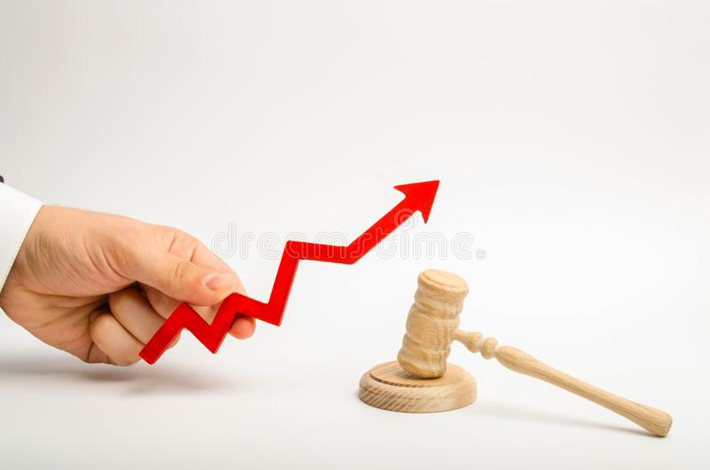The hand holds the arrow up near the judge`s hammer. The concept of increasing the percentage of disclosure of criminal cases, th. E last percent of accusatory royalty free stock images