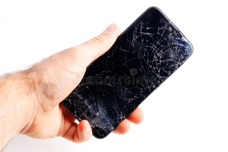Hand holds a broken smartphone on a white background stock photography