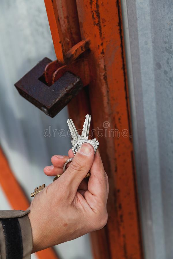 Padlock and broken key on keychain. Hand holds a bunch of keys. One key has broken. In the background gates closed by a padlock stock photo
