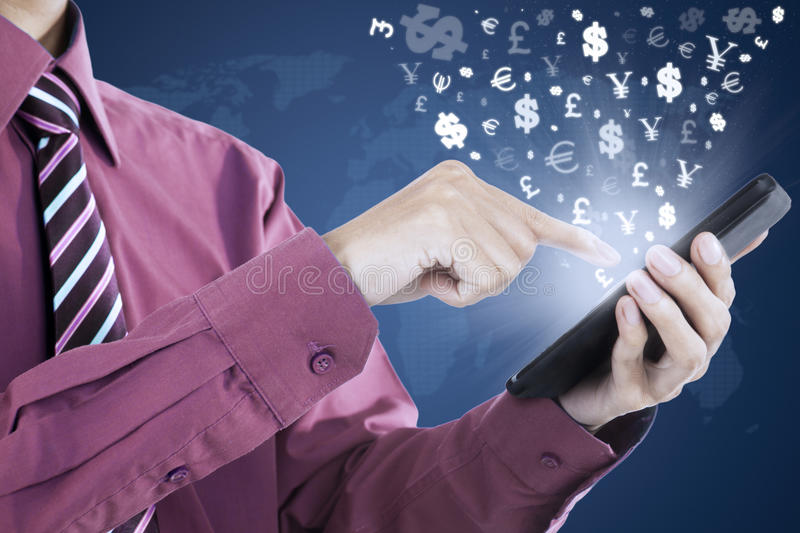 Hand holds cellular phone with currency symbols royalty free stock image