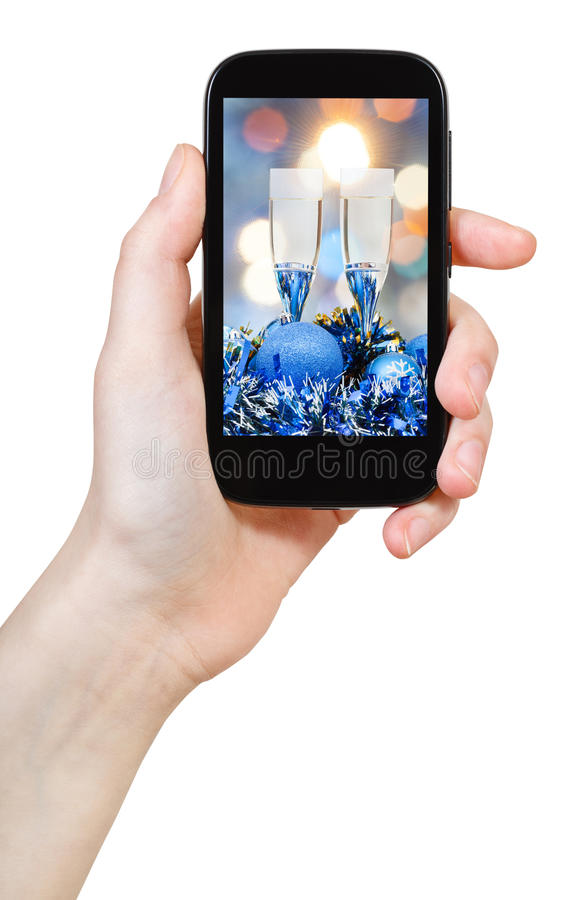 Hand holds cellular phone with Xmas still life stock image