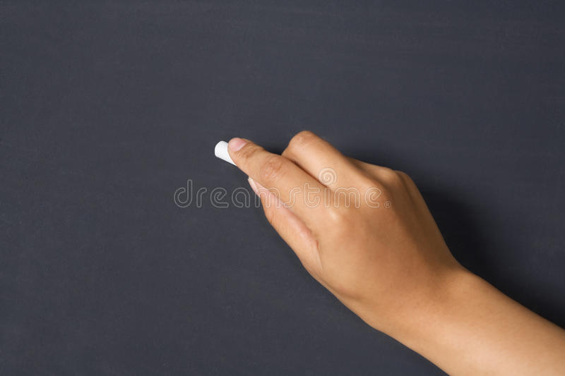 Hand holds chalk on blackboard royalty free stock image
