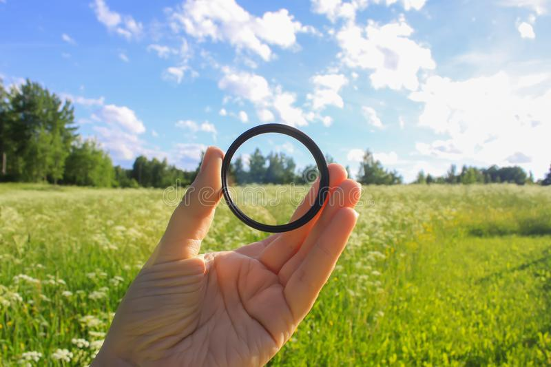 Hand holds a polarizer filter on summer landscape background. Hand holds a circular polarizer filter on summer landscape background stock photo