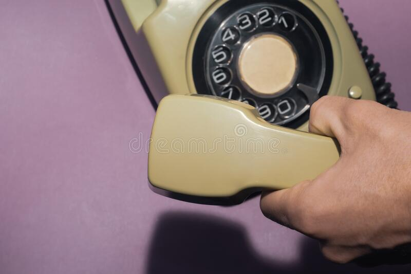 Hand holds classic telephone receiver. vintage phone with handset on color background. old communication technology. Copy space stock photo