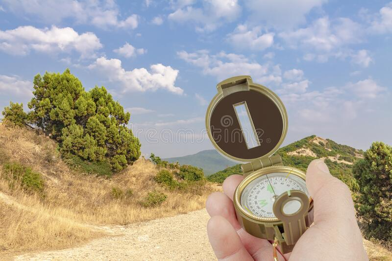 A hand holds a compass on a background of mountains, trees, bushes and sky stock photography