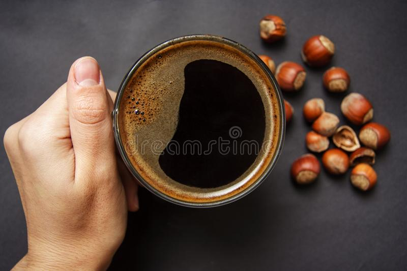 Hand holds a cup of hot coffee with foam against the hazelnut royalty free stock image