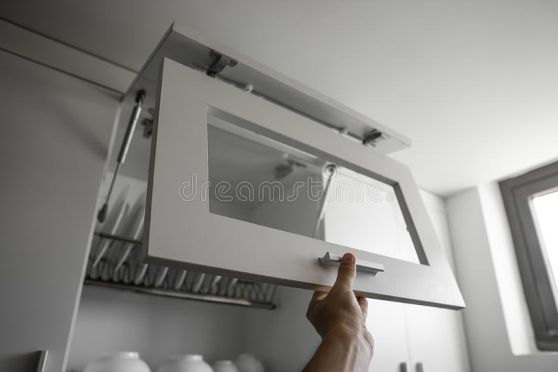 Hand holds the door of the dryer with utensils. Dish drying metal rack with white clean plates. Traditional comfortable. Kitchen. Open white dish draining stock image