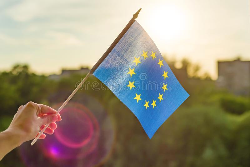 Hand holds European Union flag in an open window. Background blue sky, silhouette of the city, sunset.  royalty free stock photography
