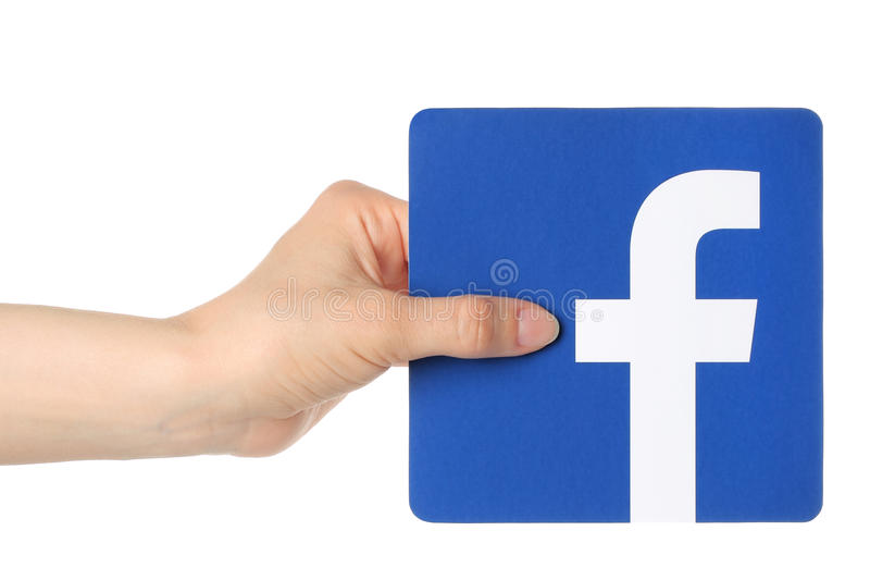 Hand holds facebook logo printed on paper on white background. KIEV, UKRAINE - APRIL 30, 2015: Hand holds facebook logo printed on paper on white background royalty free stock photo