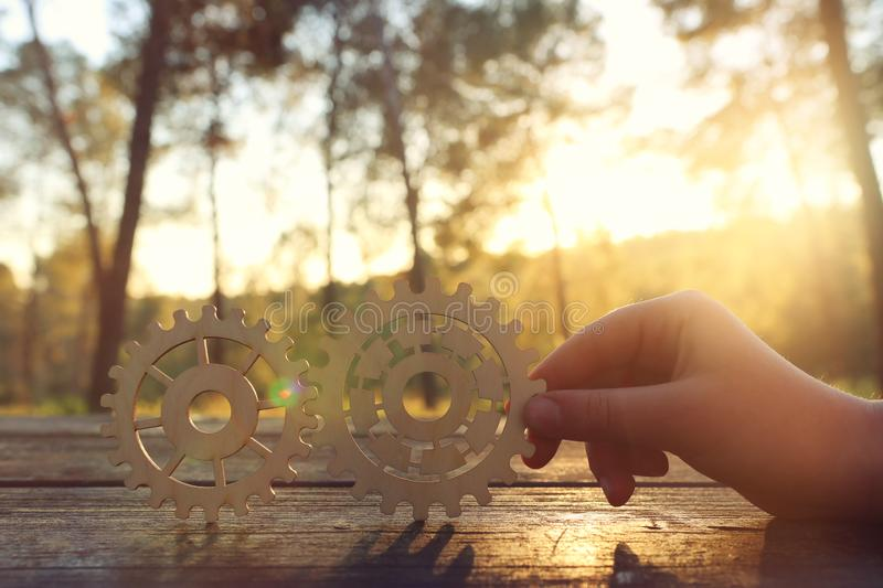 A hand holds gears in front of a setting sun. Concept of a new idea, learning and creative though. Wheel industry business cogwheel engineering technology royalty free stock photo