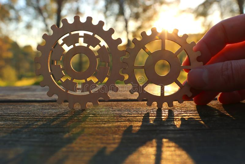 A hand holds gears in front of a setting sun. Concept of a new idea, learning and creative though. Wheel industry business cogwheel engineering technology stock photos