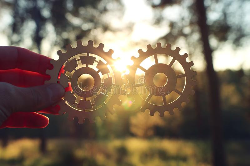 A hand holds gears in front of a setting sun. Concept of a new idea, learning and creative though. Wheel industry business cogwheel engineering technology stock image