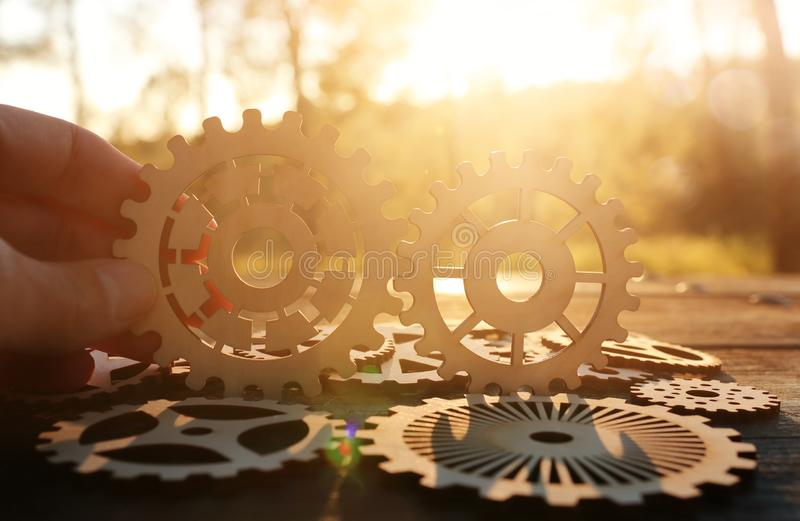 A hand holds gears in front of a setting sun. Concept of a new idea, learning and creative though. Wheel industry business cogwheel engineering technology stock photography