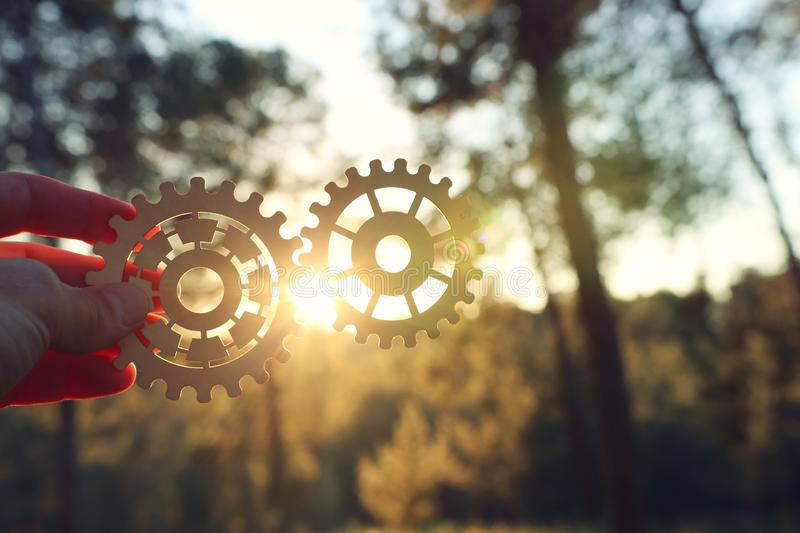 A hand holds gears in front of a setting sun. Concept of a new idea, learning and creative though. Wheel industry business cogwheel engineering technology royalty free stock photography