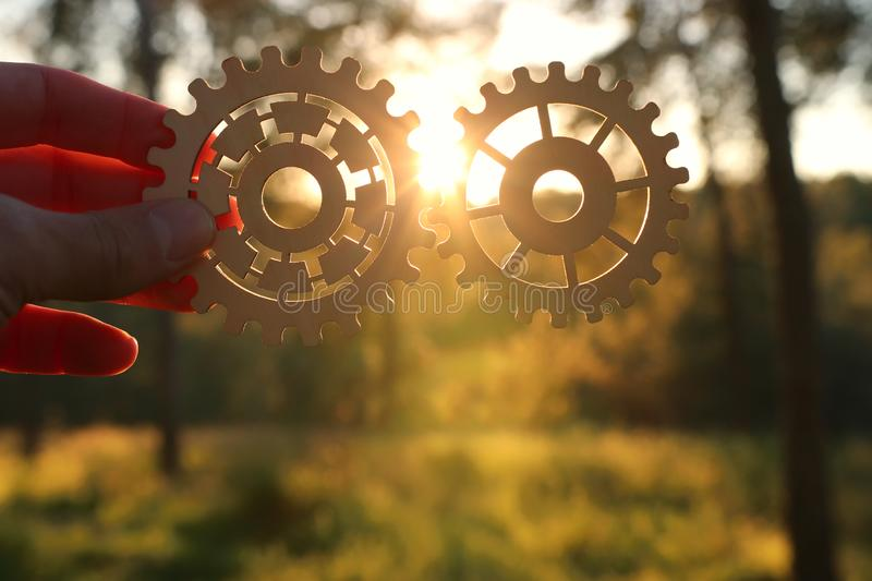 A hand holds gears in front of a setting sun. Concept of a new idea, learning and creative though. Wheel industry business cogwheel engineering technology royalty free stock images