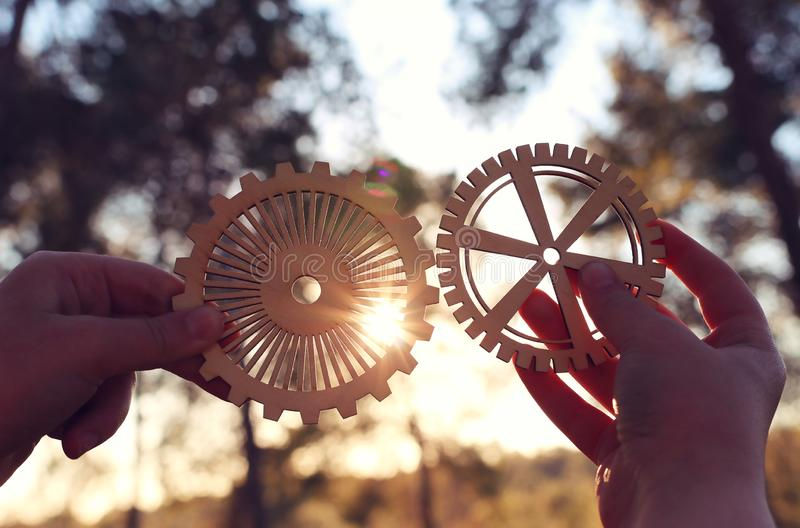 A hand holds gears in front of a setting sun. Concept of a new idea, learning and creative though. Abstract background business cog cogwheel communication stock photos