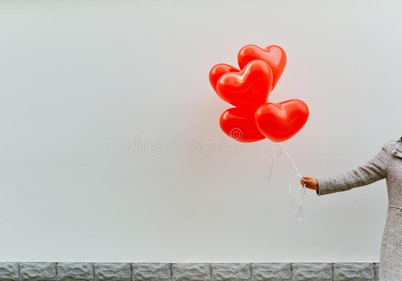 A hand holds a heart balloons against a white wall background. stock images
