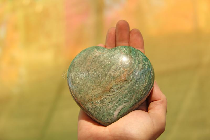 The hand holds the heart from a natural marble stone or green aventurine. Heart in hand. A stone in the shape of a heart. Love stock photography