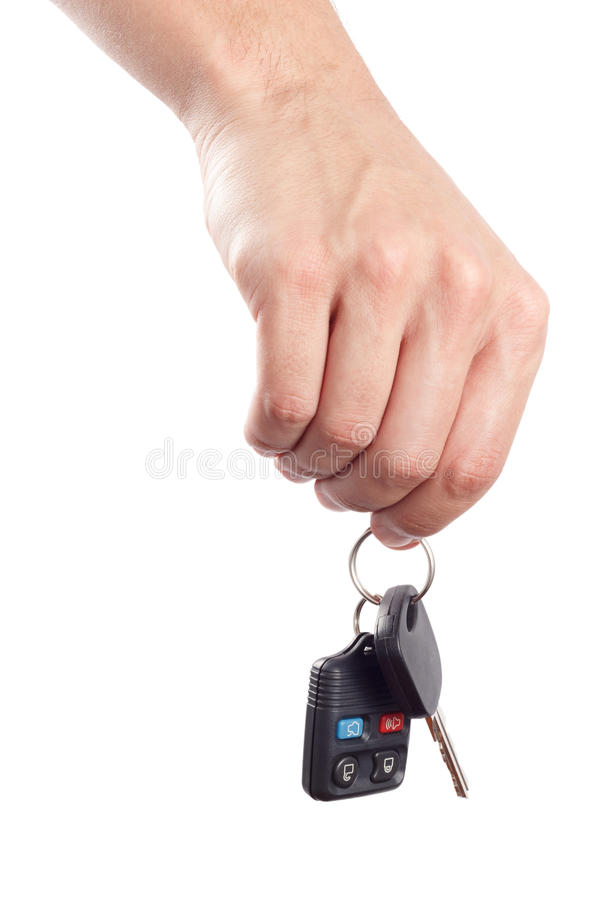 Hand holds key and remote control. Male hand holds a car key and an alarm control isolated on white background royalty free stock photo