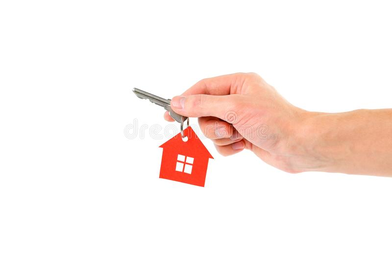 The hand holds the keys with the red house keychain. Purchase of royalty free stock image