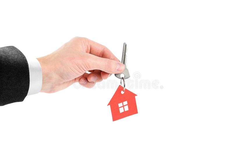 The hand holds the keys with the red house keychain. Purchase of apartments. House in hands. Close up. Isolated on a white stock photos