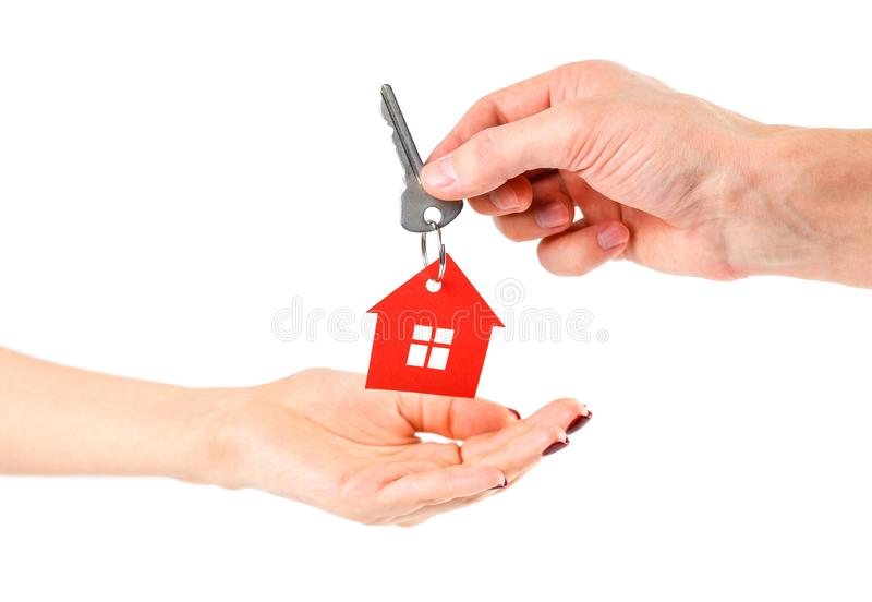 The hand holds the keys with the red house keychain. Purchase of. Apartments. House in hands. Close up. Isolated on a white background royalty free stock images