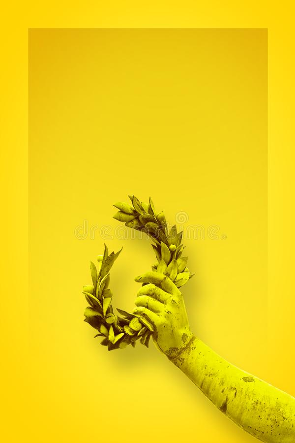Hand holds a laurel wreath - bronze statue on solid color backgr. Ound - Success and fame concept image with copy space stock photography