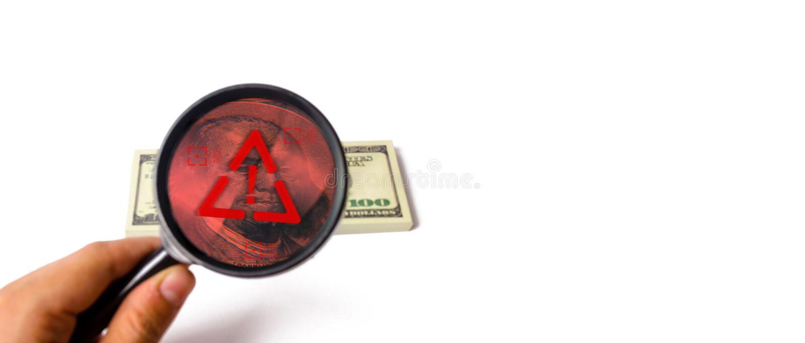 The hand holds a magnifying glass and looks bundle of dollars. suspicious cash traffic. Laundering of money. Fake money stock photos