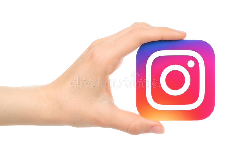 Hand holds new Instagram logo printed on paper. Kiev, Ukraine - May 18, 2016: Hand holds new Instagram logo printed on paper, on white background. Instagram is stock image