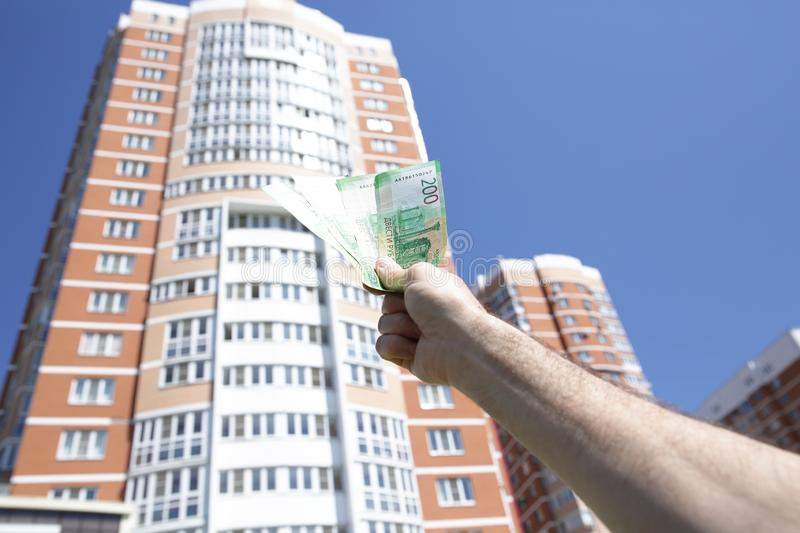 Hand holds a new Russian banknote two hundred rubles on the background of a big building and blue sky. Cash paper money royalty free stock images