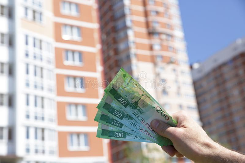 Hand holds a new Russian banknote two hundred rubles on the background of a big building and blue sky. Cash paper money stock photos